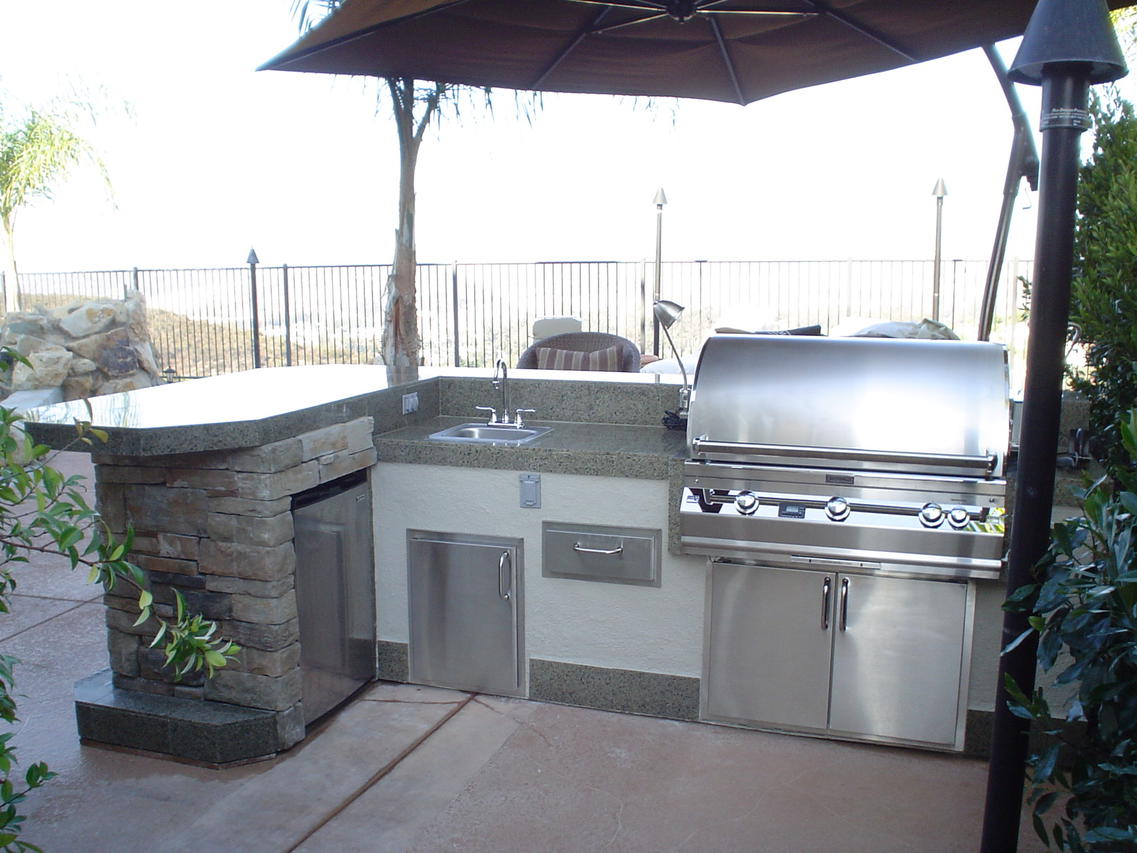 15′ outdoor kitchen featuring a 660i Fire Magic grill, sink, single ...